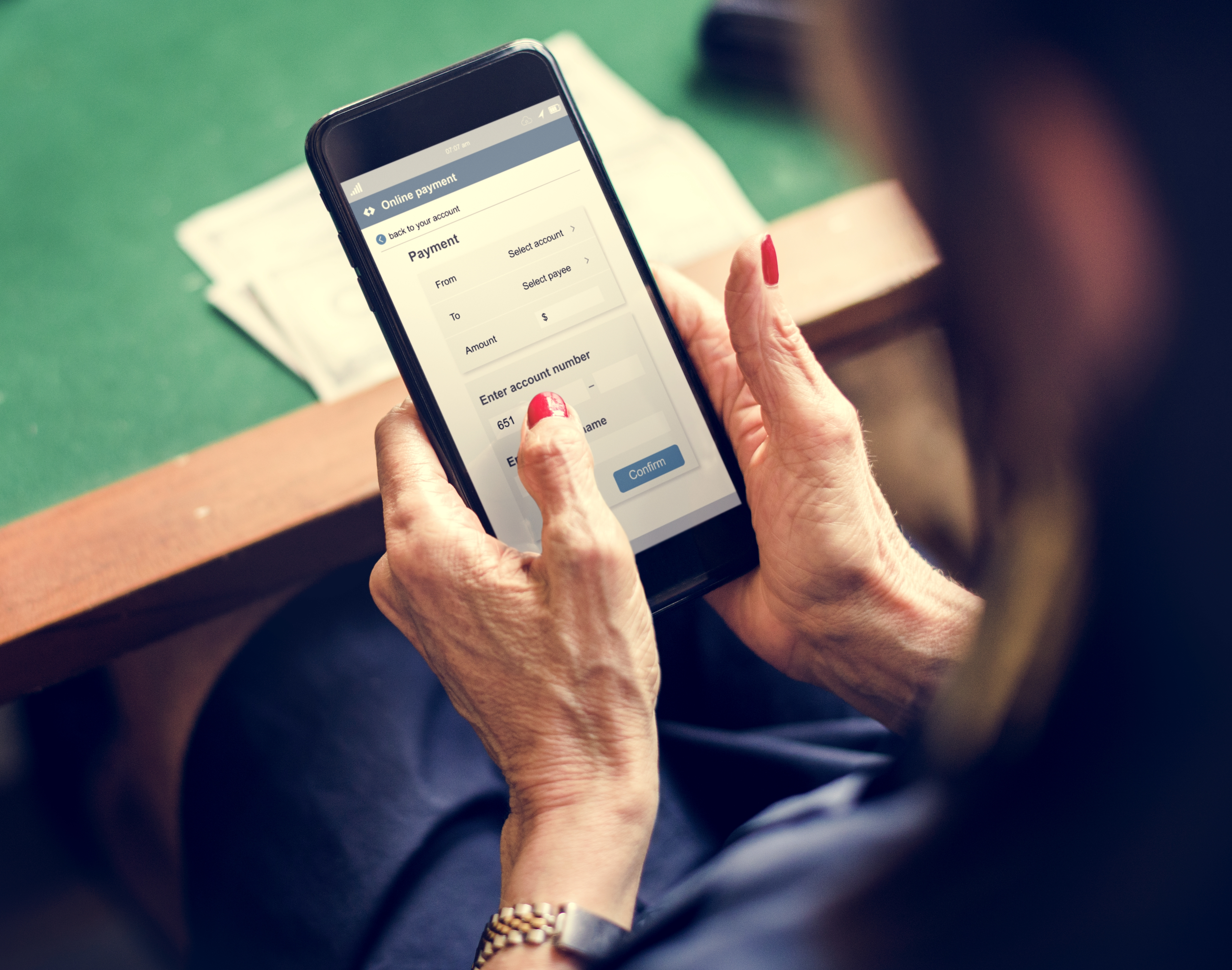 Hands holding smartphone paying online
